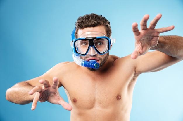 Młody śmieszny mężczyzna bawić się z rękami i jest ubranym maskę wodną