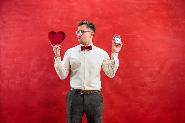 Młody śmieszny mężczyzna z abstrakcjonistycznym sercem i zegarem