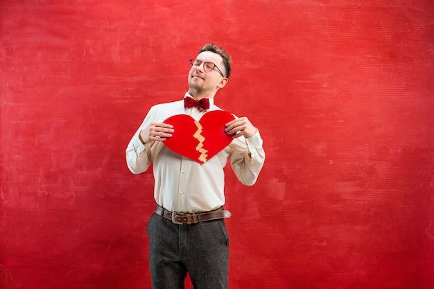 Młody śmieszny mężczyzna z abstrakcjonistycznym złamanym sercem