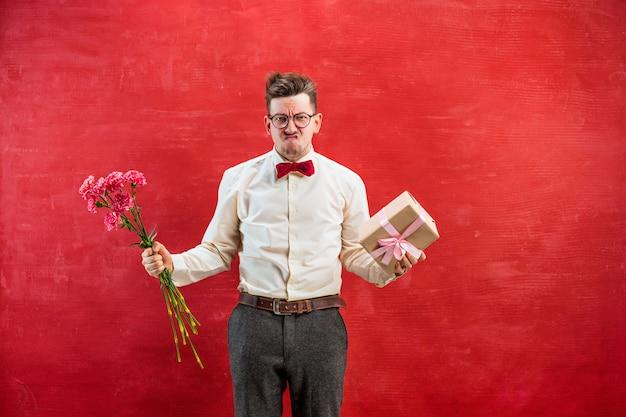 Młody śmieszny mężczyzna z kwiatami i prezentem