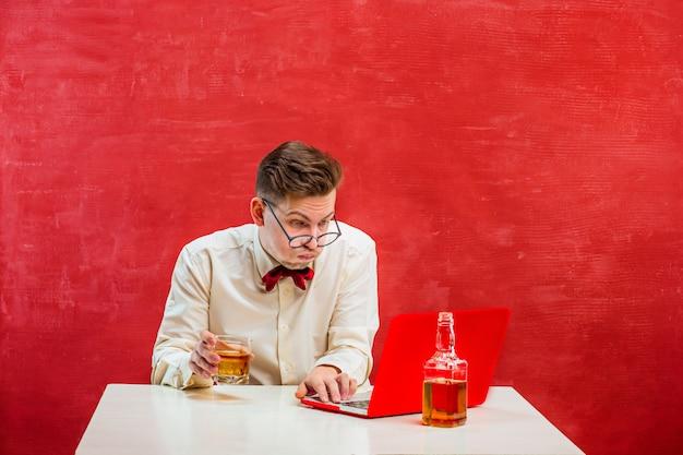 Młody śmieszny mężczyzna z laptopem przy st. walentynki