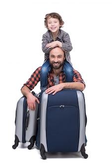 Młody śmieszny ojciec i syn z bagażem.