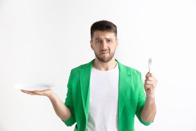 Młody smutny atrakcyjny kaukaski facet trzyma puste naczynie i widelec na białym tle na szarym tle. skopiuj miejsce i mock up. puste tło szablonu. odrzuć, koncepcja odrzucenia