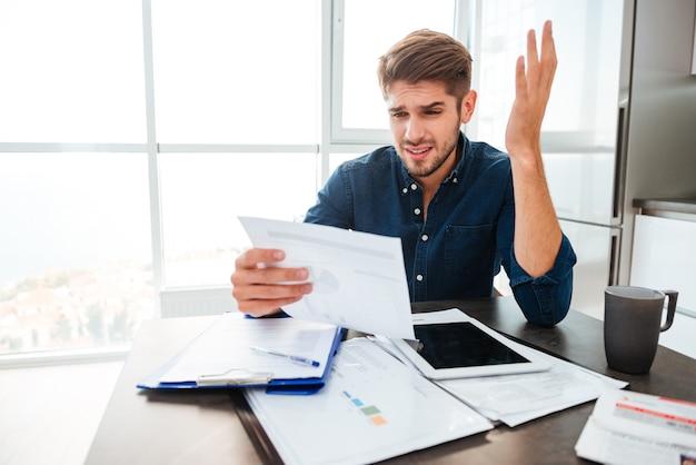 Młody smutny mężczyzna analizuje finanse domowe, gestykulując ręką i patrząc na dokumenty