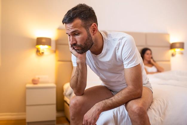 Młody smutny mężczyzna siedzi na łóżku po kłótni z żoną