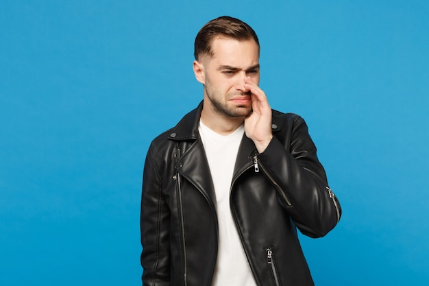 Młody smutny sfrustrowany zmartwiony nieogolony mężczyzna w czarnej kurtce biały t-shirt patrząc aparat na białym tle na tle niebieskiej ściany portret studio. koncepcja życia szczere emocje ludzi. makieta miejsca na kopię.