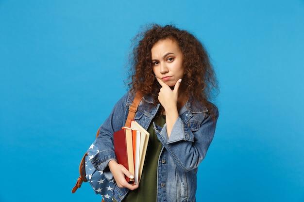 Młody Smutny Student W Dżinsowych Ubraniach I Plecaku Trzyma Książki Izolowane Na Niebieskiej ścianie Darmowe Zdjęcia