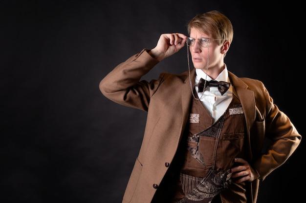 Młody, solidny mężczyzna na podobieństwo wiktoriańskiego naukowca, nauczyciela akademickiego lub przyrodnika. vintage retro garnitur, młody atrakcyjny mężczyzna w kamizelce i muszce