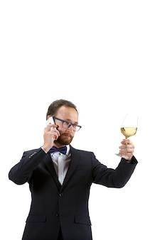Młody sommelier polerujący kieliszek do wina, rozmawiając telefon na białym tle.