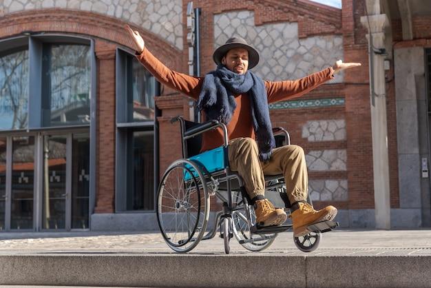 Młody sparaliżowany mężczyzna na wózku inwalidzkim sfrustrowany przed schodami