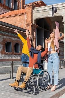 Młody sparaliżowany mężczyzna z ameryki łacińskiej na wózku inwalidzkim obok dwóch szczęśliwych młodych dziewcząt rasy kaukaskiej podrzucających kapelusz w powietrze, gdy spacerują ulicą