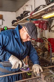 Młody spawacz w niebieskiej koszulce, goglach i rękawicach budowlanych przetwarza metal w szlifierce kątowej w garażu