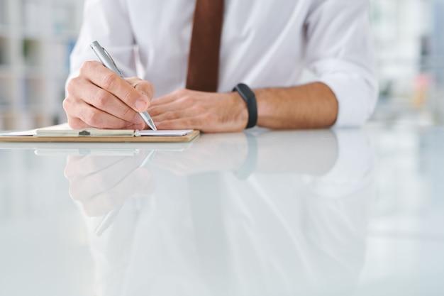 Młody specjalista z długopisem i schowkiem zapisujący plan pracy lub szkicujący przy biurku