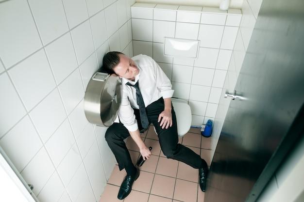 Młody śpi pijany mężczyzna w toalecie