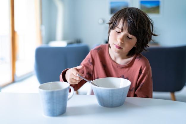 Młody śpiący chłopiec w piżamie, spożywający śniadanie w domu rano przed szkołą. zdrowa żywność dla dzieci.