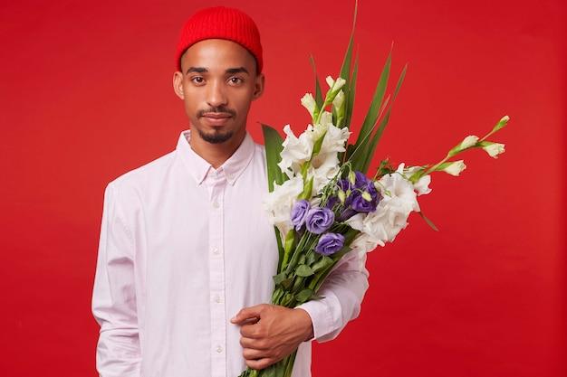 Młody spokojny afroamerykanin facet w białej koszuli i czerwonym kapeluszu, trzyma bukiet, stoi na czerwonym tle i patrzy w kamerę.