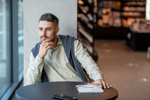 Młody spokojny biznesmen lub student czekający na kogoś w księgarni