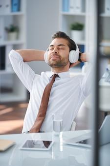 Młody spokojny biznesmen słuchanie relaksującej muzyki w słuchawkach, ciesząc się przerwą przy biurku