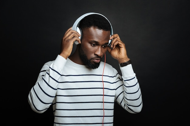 Młody spokojny człowiek za pomocą słuchawek i słuchania muzyki, stojąc odizolowane od czarnej ściany