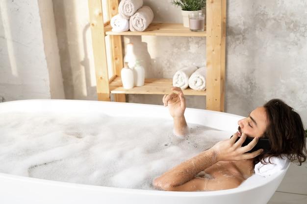 Młody spokojny mężczyzna rozmawia przez smartfona, leżąc w wannie wypełnionej wodą i pianą w łazience
