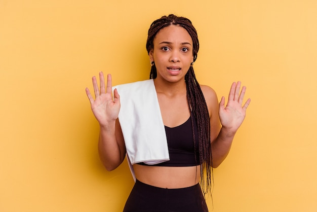 Młody sport afroamerykanin kobieta trzyma ręcznik na białym tle na żółtym tle odrzucając kogoś pokazującego gest obrzydzenia.