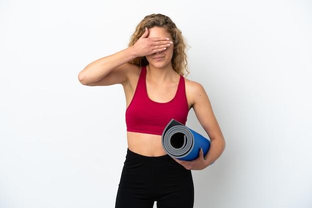 Młody sport blond kobieta idzie na zajęcia jogi trzymając matę na białym tle na białym tle zasłaniając oczy rękami. nie chcę czegoś widzieć
