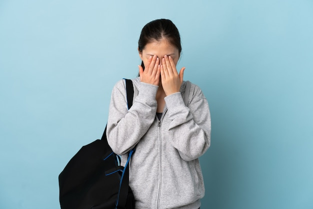 Młody sport chinka z torbą sportową na białym tle z wypowiedzi zmęczony i chory