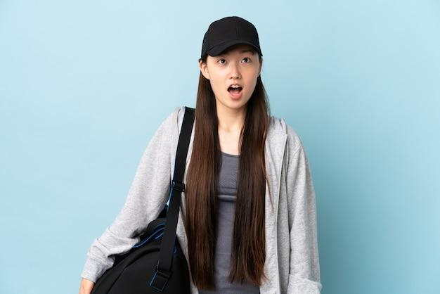 Młody sport chinka z torbą sportową na niebieską ścianą patrząc i zaskoczony wyrażenie