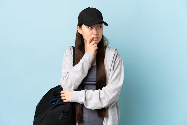 Młody sport chinka z torbą sportową na niebieskiej ścianie, nerwowa i przestraszona