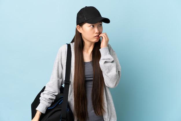 Młody sport chinka z torbą sportową na niebieskim tle jest trochę zdenerwowana