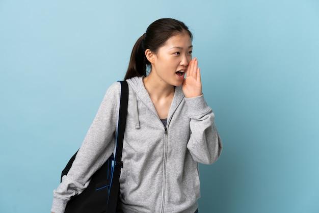 Młody sport chinka z torbą sportową na pojedyncze niebieskie krzyczy z szeroko otwartymi ustami z boku