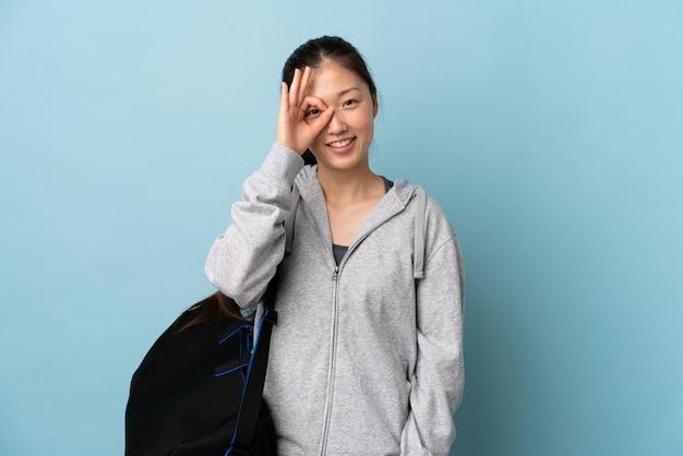 Młody sport chinka z torbą sportową na pojedyncze niebieskie pokazuje ok znak palcami