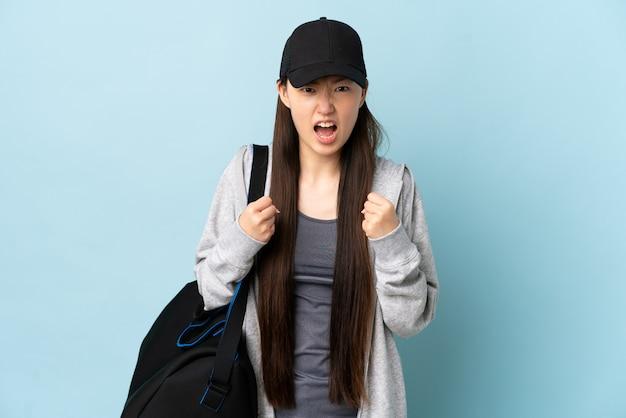 Młody sport chinka z torbą sportową na pojedyncze niebieskie sfrustrowane złą sytuacją