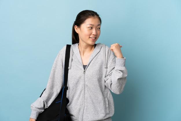 Młody sport chinka z torbą sportową na pojedyncze niebieskie skierowane w bok, aby przedstawić produkt
