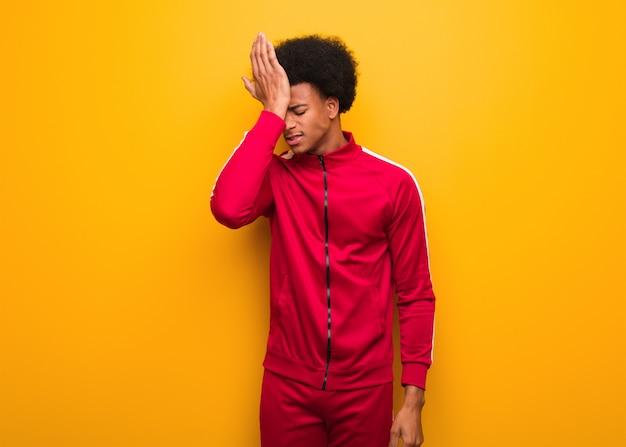 Młody sport czarny człowiek zapomina o pomarańczowej ścianie, zdaje sobie sprawę