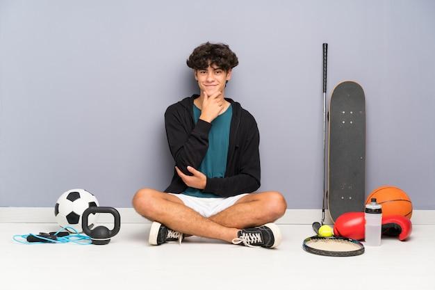 Młody sport człowiek siedzi na podłodze wokół wielu elementów sportowych śmiejąc się