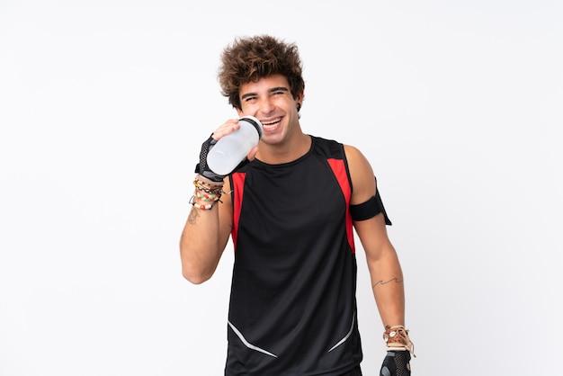 Młody sport człowiek z tatuażami na pojedyncze białe ściany z butelką wody sportowe