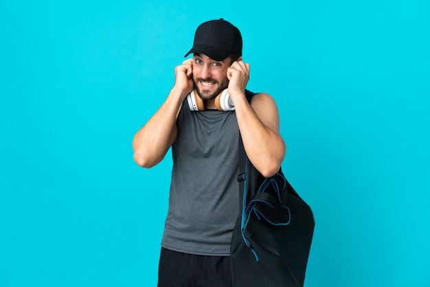 Młody sport człowiek z torbą sportową na niebieskim ścianie sfrustrowany i obejmujące uszy