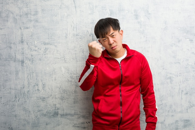 Młody sport fitness chiński pokazując pięść do przodu, zły wyraz