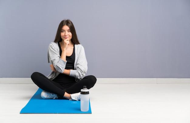 Młody sport kobieta siedzi na podłodze z mat śmiejąc się