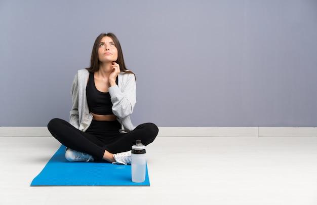 Młody sport kobieta siedzi na podłodze z matą myślenie pomysł
