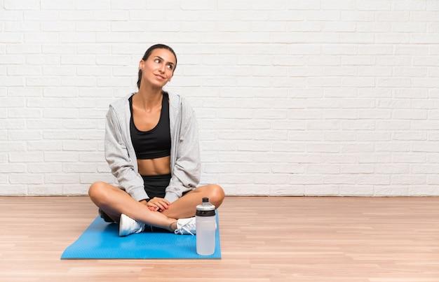Młody sport kobieta siedzi na podłodze z matą, śmiejąc się i patrząc w górę