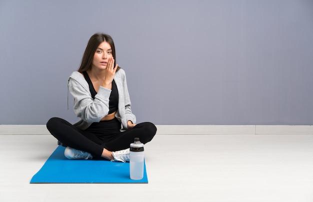 Młody sport kobieta siedzi na podłodze z matą szepcząc coś