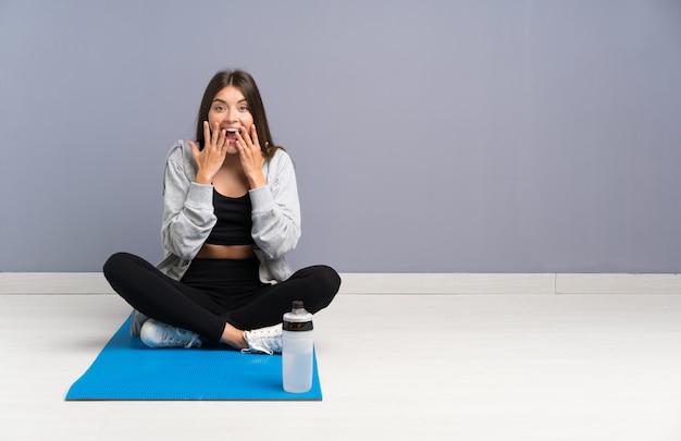 Młody sport kobieta siedzi na podłodze z matą z zaskoczenia wyraz twarzy