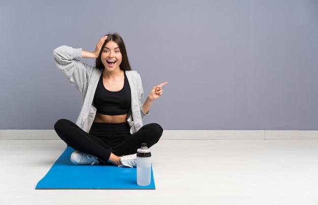 Młody sport kobieta siedzi na podłodze z matą zaskoczony i wskazując palcem na bok