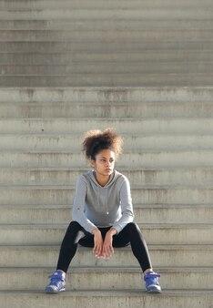 Młody sport kobiety obsiadanie na schodkach outdoors