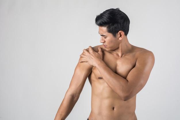 Młody sport mężczyzna z bólem w ramieniu.