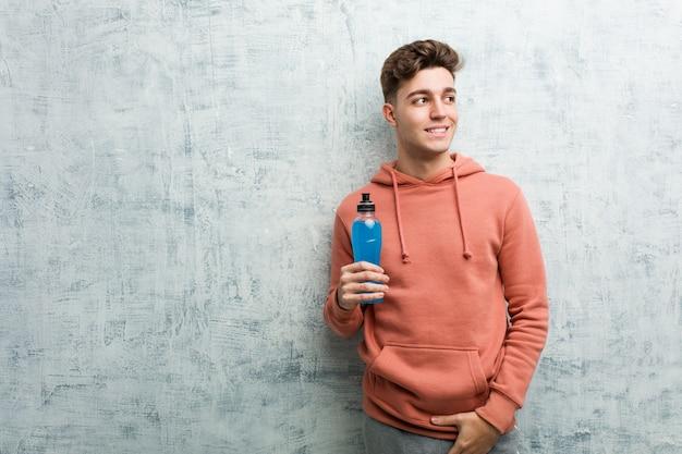 Młody sporta mężczyzna trzyma napoju energetycznego ono uśmiecha się ufny z krzyżować rękami.