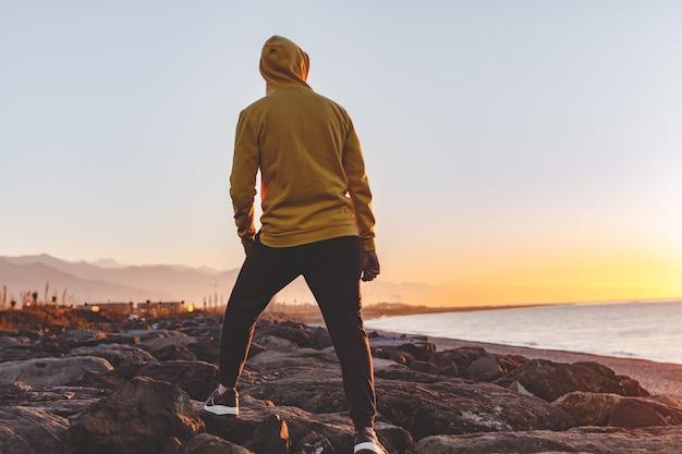 Młody sporta mężczyzna w kapiszonie robi skokowi na skałach na morza i gór tle przy zmierzchem