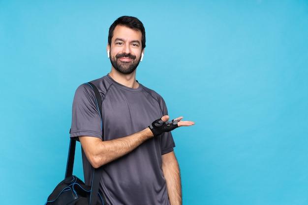 Młody sporta mężczyzna z brodą nad odosobnioną błękit ścianą przedstawia pomysł podczas gdy patrzejący uśmiecha się w kierunku